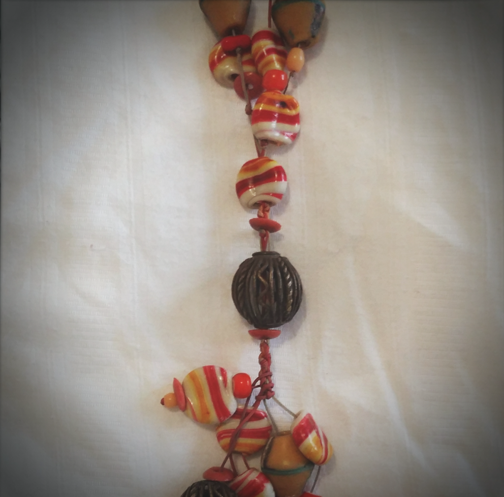 My 'gypsy' necklace was hand made in Ghana and purchased at the Suntrade Centre. It hangs past my navel and is made out of brass, plastic and recycled glass beads.